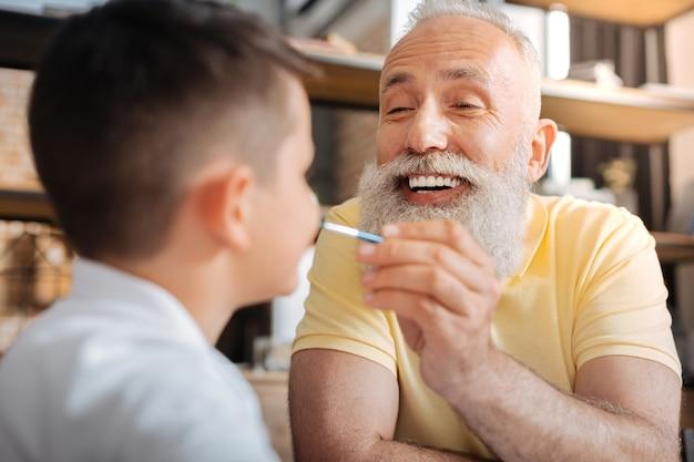 Młoda dusza. zadowolony starszy mężczyzna trzymający pędzelek i nakładający kropki farby akwarelowej na nos wnuka, bawiąc się z nim