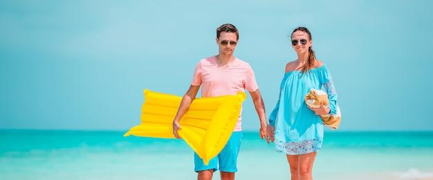 Młoda dwuosobowa rodzina na białej plaży świetnie się bawi