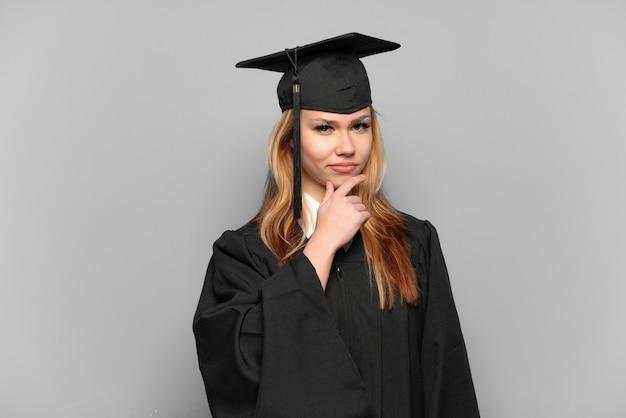 Młoda dziewczyna absolwent uniwersytetu na białym tle myślenia