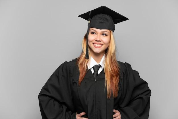 Młoda dziewczyna absolwent uniwersytetu na białym tle stwarzających z rękami na biodrze i uśmiechnięty