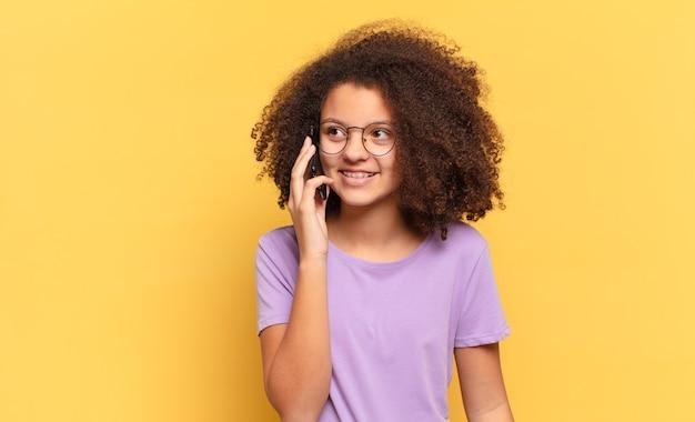 Młoda dziewczyna afro nastolatka za pomocą swojej komórki