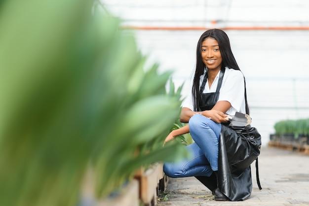 Młoda dziewczyna afroamerykanów, pracownik z kwiatami w szklarni.