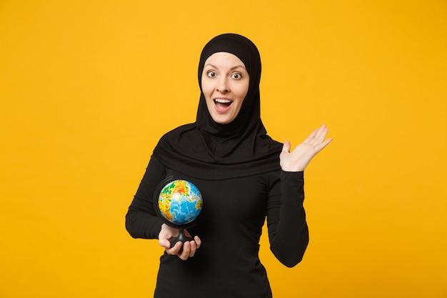 Młoda dziewczyna arabskich studentów muzułmańskich w hidżab czarne ubrania trzymać w rękach globus ziemi na białym tle portret żółtej ściany. koncepcja życia religijnego ludzi.
