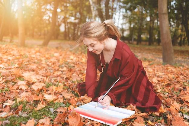 Młoda dziewczyna artysta rysuje zdjęcie klęczące w parku na trawie.