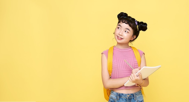 Młoda dziewczyna azjatyckich dziecko myślenia i pisania coś na notebooku na białym tle na żółtym tle.