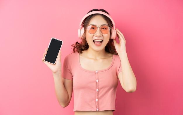 Młoda dziewczyna azjatyckich noszenie słuchawek i używanie telefonu na różowo