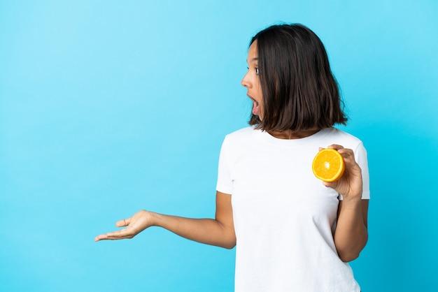 Młoda dziewczyna azjatyckich trzyma pomarańczowy na białym tle na niebieskiej ścianie z wyrazem zaskoczenia, patrząc z boku