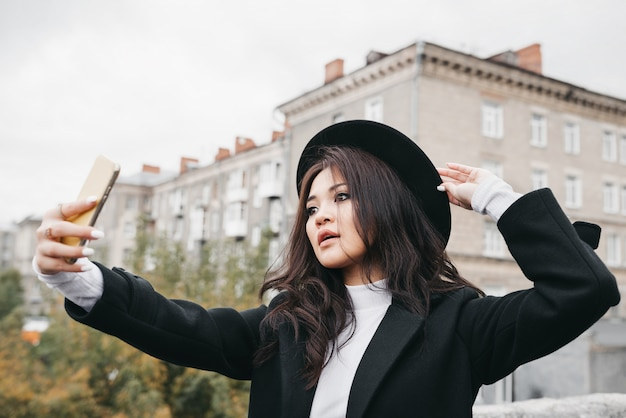 Młoda dziewczyna azjatyckich w ciemny płaszcz i kapelusz
