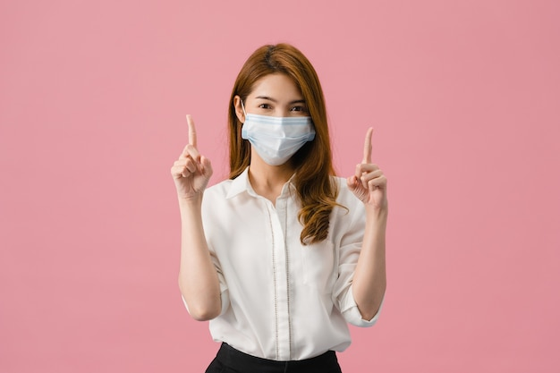Młoda dziewczyna azji nosząca maseczkę medyczną pokazuje coś w pustej przestrzeni, ubrana w zwykłą szmatkę i patrząc na kamerę na białym tle na różowym tle.