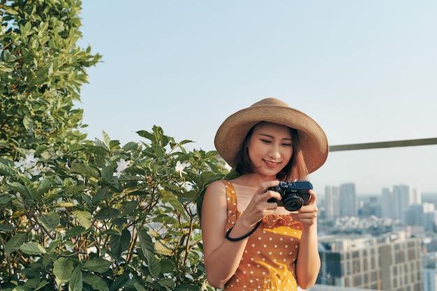 Młoda dziewczyna azji stojąc na dachu i za pomocą aparatu, aby zrobić zdjęcie. koncepcja lato.