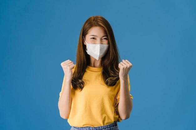 Młoda dziewczyna azji ubrana w medyczną maskę na twarz pokazującą znak pokoju, zachęca ubrana w zwykły materiał i patrząc na aparat na niebieskim tle. dystans społeczny, kwarantanna dla wirusa koronowego.