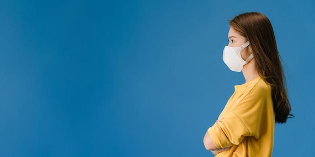 Młoda dziewczyna azji ubrana w medyczną maskę na twarz ubrana w zwykłą szmatkę i spojrzeć na puste miejsce na białym tle na niebieskim tle. dystans społeczny, kwarantanna dla wirusa koronowego. panoramiczne tło transparent.