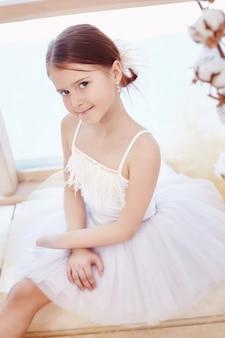 Młoda dziewczyna baleriny przygotowuje się do spektaklu baletowego. mały balet prima. dziewczyna w białej balowej sukni i pointe w pobliżu okna, piękne rude włosy