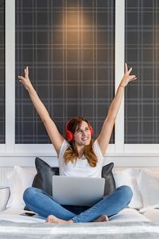 Młoda dziewczyna bardzo szczęśliwa z rękami do góry, siedząc na łóżku, słuchając muzyki i pracując na swoim laptopie