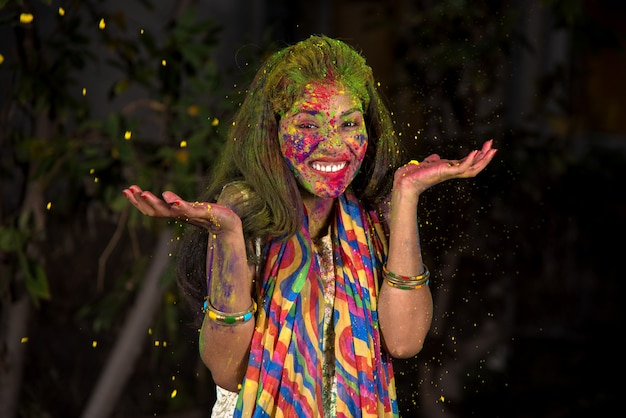 Młoda dziewczyna bawi się kolorami. koncepcja indyjskiego festiwalu holi. plusk koloru.