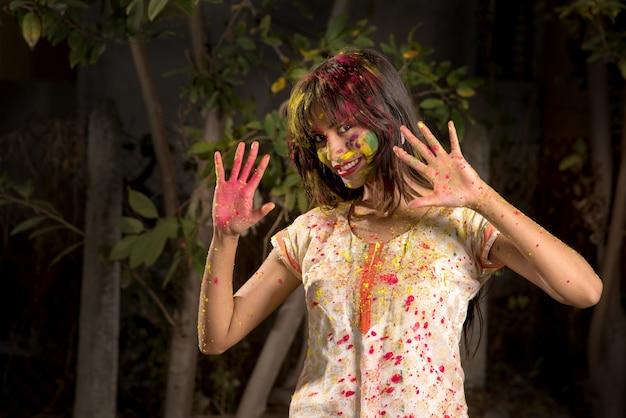 Młoda dziewczyna bawi się kolorami z okazji holi. koncepcja indyjskiego festiwalu holi. plusk koloru.