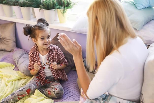 Młoda dziewczyna bawi się z matką w pobliżu okna