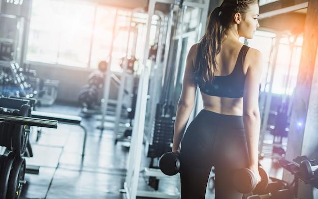 Młoda dziewczyna bawić się dumbbell ćwiczyć w sprawności fizycznej