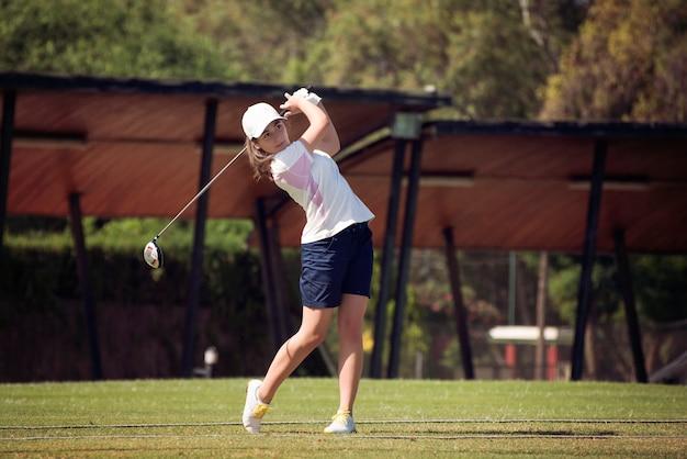 Młoda dziewczyna bawić się golfa na słonecznym dniu