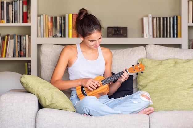 Młoda dziewczyna bawić się ukulele obsiadanie w kanapie w domu