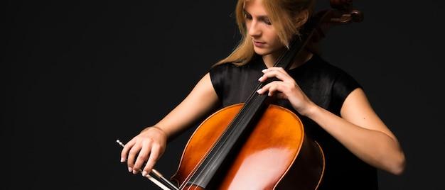 Młoda dziewczyna bawić się wiolonczelę na odosobnionym czarnym tle