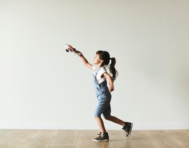 Młoda dziewczyna bawić się z zabawkarskim samolotem