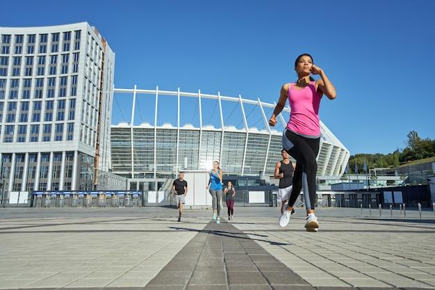 Młoda dziewczyna biegająca przed innymi sportowcami