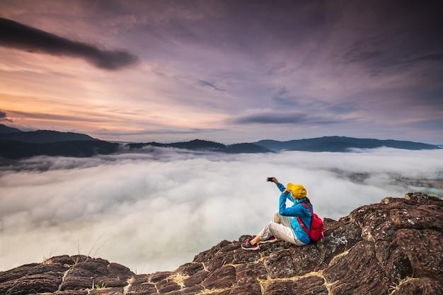 Młoda dziewczyna bierze fotografie morze mgła na wysokiej górze.
