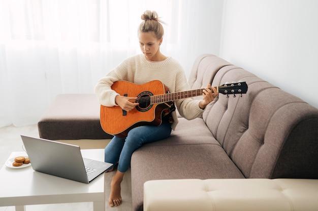Młoda dziewczyna bierze lekcję gry na gitarze online