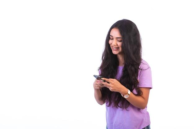 Młoda dziewczyna, biorąc selfie lub nawiązywanie połączenia wideo na białej ścianie.