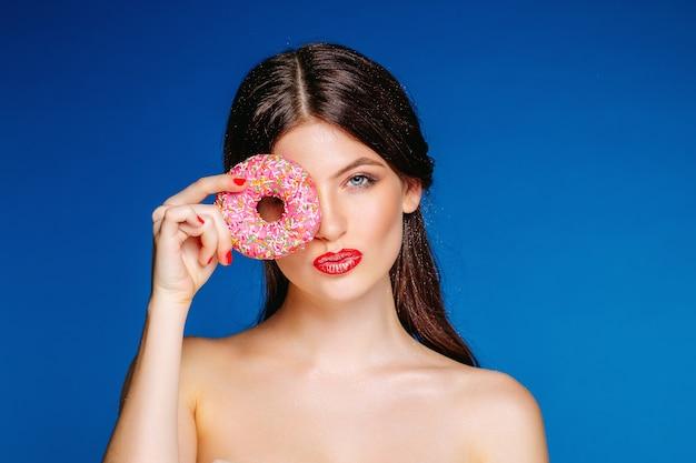 Młoda dziewczyna brunetka model na tle jasnoniebieskiej ściany