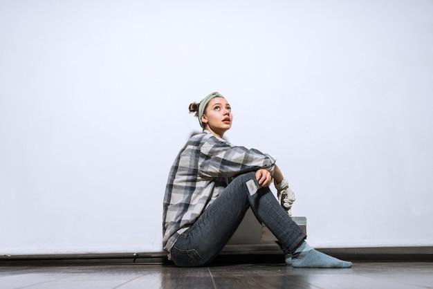 Młoda dziewczyna budowlana w kraciastej koszuli siedzi na podłodze, zmęczona naprawami