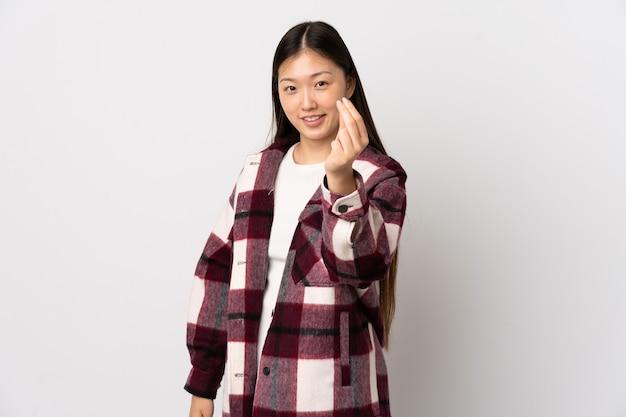 Młoda dziewczyna chiński na pojedyncze białym tle, czyniąc gest pieniędzy