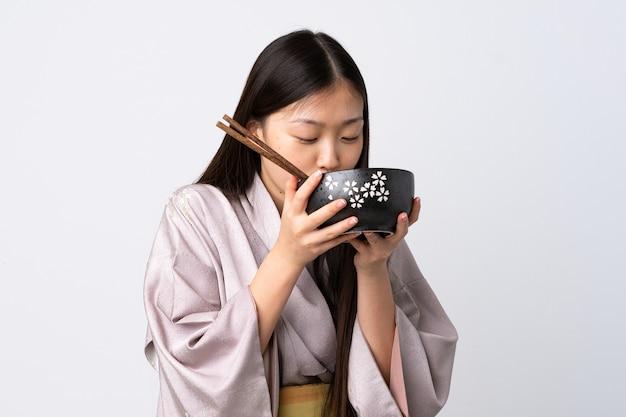 Młoda dziewczyna chiński na sobie kimono na białym tle