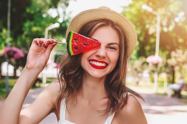 Młoda dziewczyna chodzi po parku z lizakiem w postaci arbuza. dziewczyna w słomkowym kapeluszu ono uśmiecha się w parku