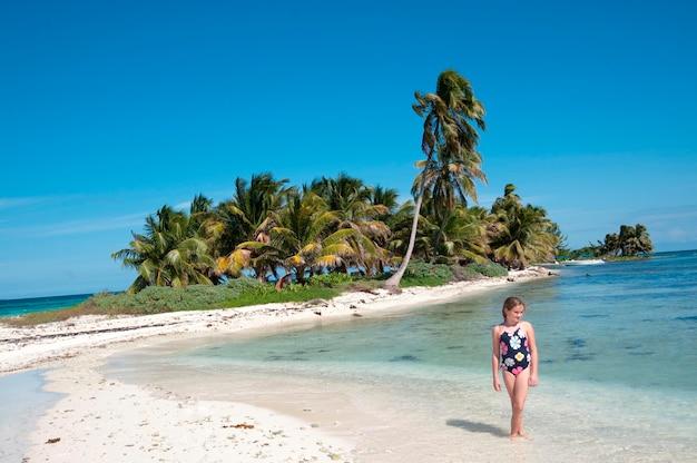 Młoda dziewczyna chodzi wzdłuż plaży przy belizean wyspą w belize