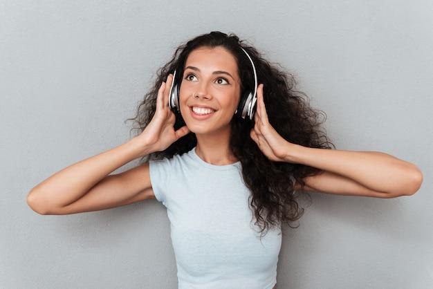 Młoda dziewczyna cieszy się muzykę w hełmofonach