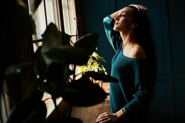 Młoda dziewczyna cieszy się wczesnym słońcem przy oknie