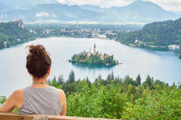 Młoda dziewczyna cieszy się zapierającym dech w piersiach widokiem na jezioro bled w słowenii. widok od tyłu.