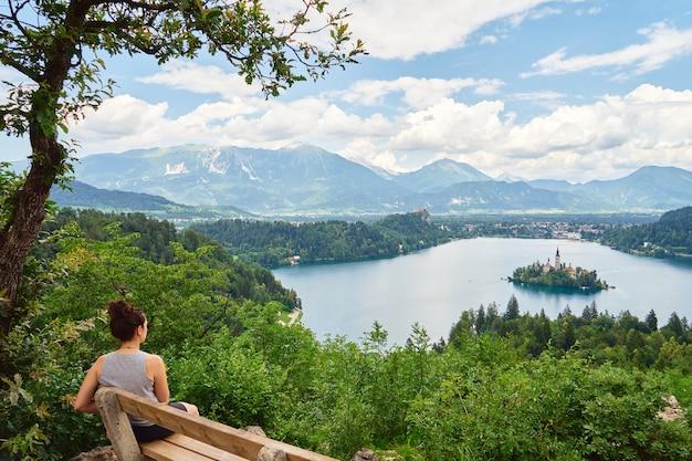 Młoda dziewczyna cieszy się zapierającym dech w piersiach widokiem na jezioro bled w słowenii. widok z boku z tyłu.