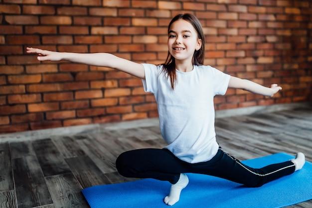Młoda dziewczyna ćwiczy jogę, ćwiczenia rozciągające, rozszerzony kąt boczny poza...