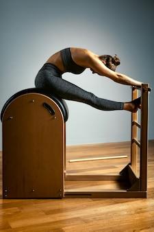 Młoda dziewczyna ćwiczy na łóżku reformatorów pilatesa, w hali na tle szarej ściany.