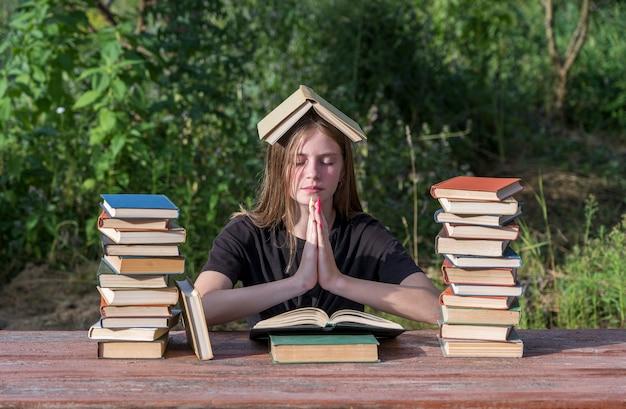 Młoda dziewczyna czyta książkę i marzenia w ogrodzie przy drewnianym stole ze stosem książek. koncepcja edukacji domowej