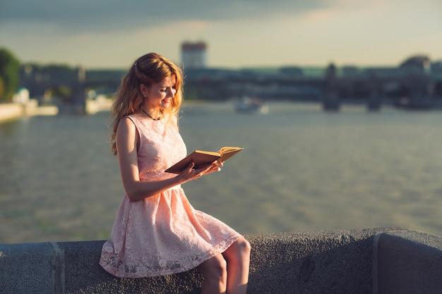 Młoda dziewczyna czyta książkę na brzegu rzeki.
