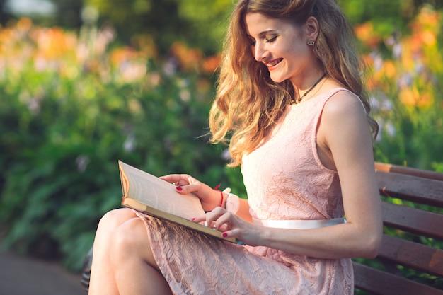 Młoda dziewczyna czyta książkę, siedząc na ławce o zachodzie słońca.