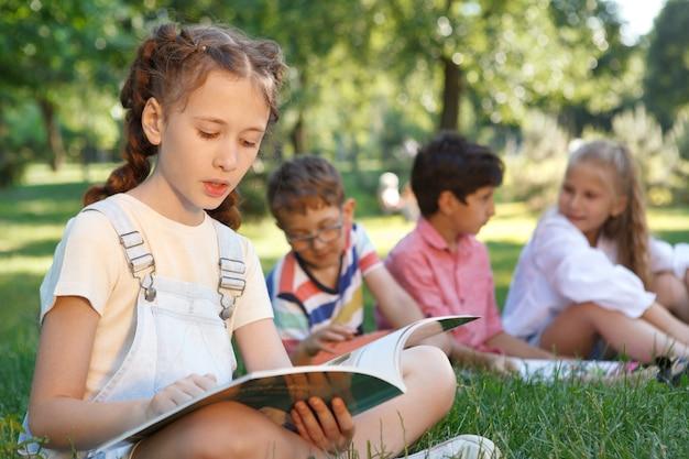 Młoda dziewczyna czyta książkę w parku, podczas gdy jej przyjaciele relaksują się na trawie