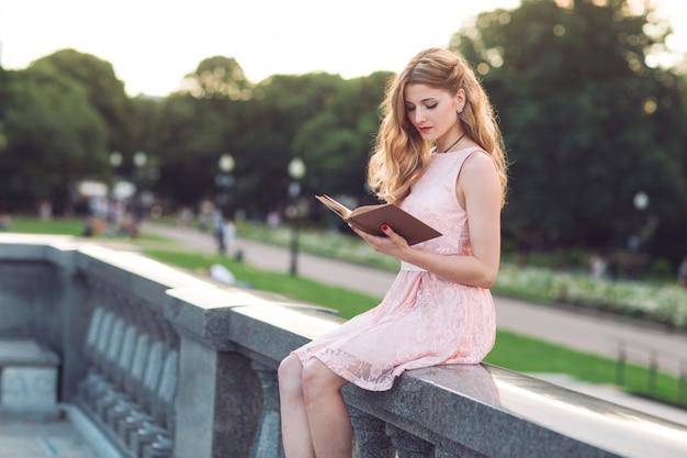 Młoda dziewczyna czyta książkę w parku.