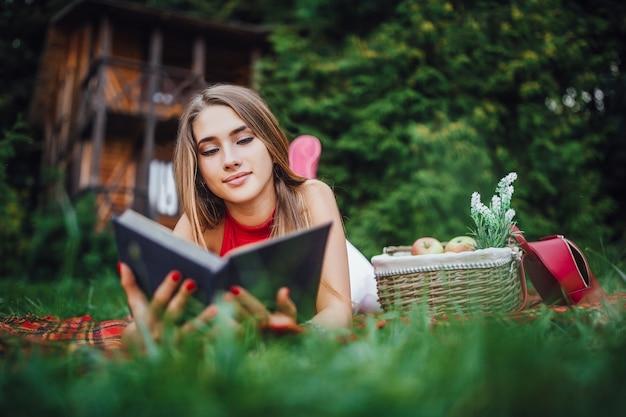 Młoda dziewczyna czyta książkę z owocami na trawie w parku