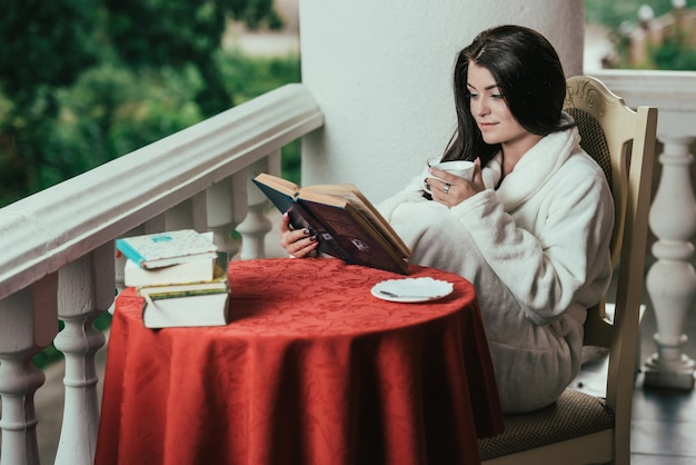 Młoda dziewczyna czytanie książki podczas picia kawy w słoneczny dzień siedząc na balkonie.