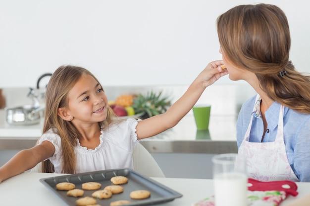 Młoda dziewczyna daje ciastku jej matka